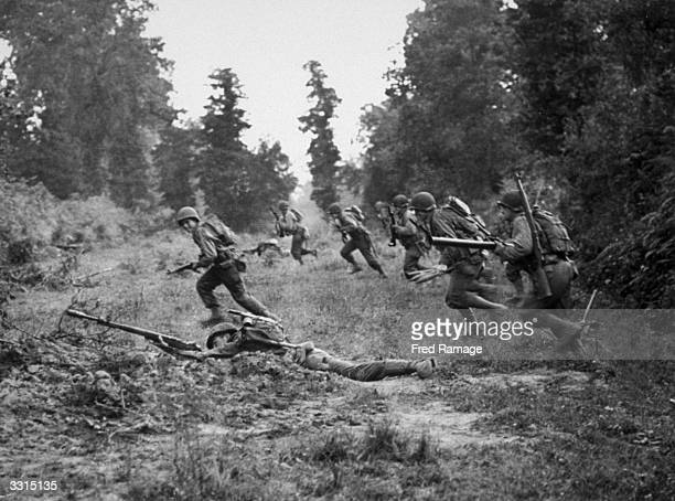 US infantrymen dash across machinegunned ground where they were facing SS troops The attack was preceded by a terrific air bombardment which forced...