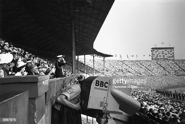 Camera films the proceedings at Wembley Stadium as King George VI takes the March Past of 6,000 athletes representing 58 countries, at the Opening...