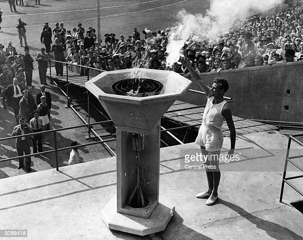 British athlete John Mark lights the Olympic Flame at the opening ceremony of the Olympic Games at Wembley Stadium, London.