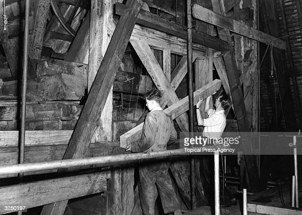 Workmen placing new timbers into position in the belfry as part of the repair and restoration work taking place at the famous Curfew Tower at Windsor...