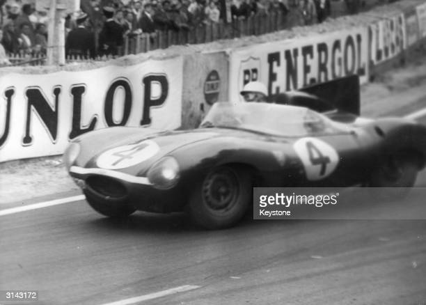 Britain's Ninian Sanderson and Ron Flockhart drive a Jaguar Dtype to victory in the Le Mans 24 hour classic