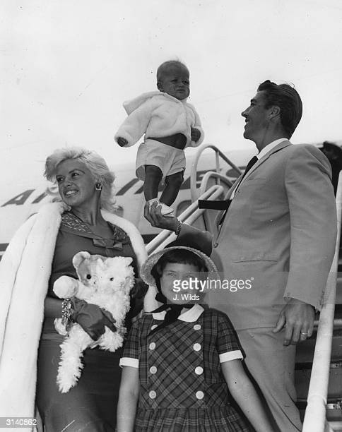Hollywood sex symbol Jayne Mansfield arrives at London Airport to star in the British film 'Too Hot To Handle' With her are her husband Mickey...