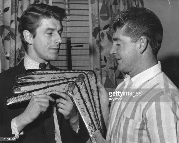 Press officer for pop group The Beatles Derek Taylor receives a set of hand decorated boomerangs on their behalf from Jack Bonwell of Brisbane a fan...