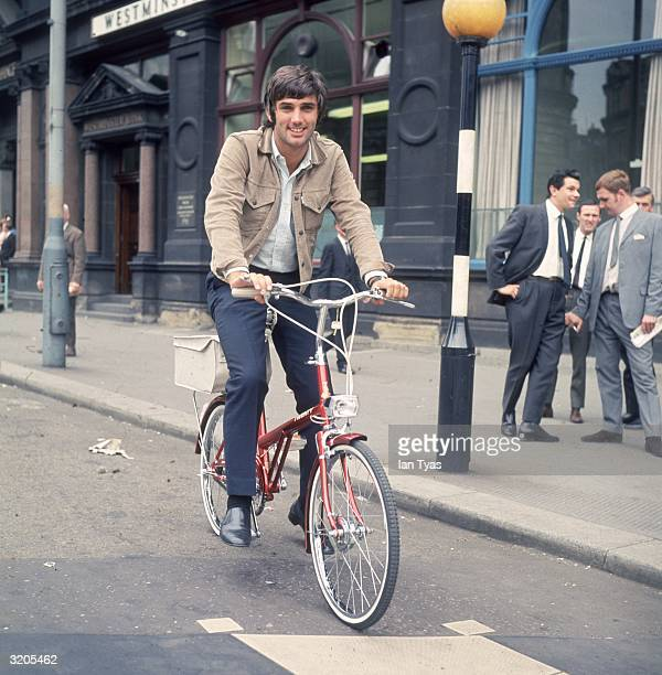 Manchester United star George Best riding a bike down the street in London after receiving a six month driving ban from a Manchester court
