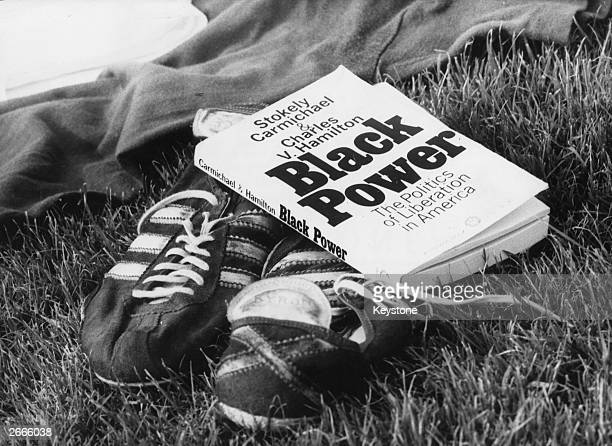 Book about black power lies next to a pair of running shoes at Neckarstadion, Stuttgart where Black-Power athletes are running in an America/Europe...