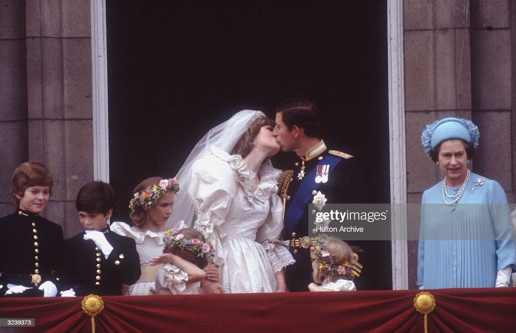 Prince Charles, Prince of Wales, kissing his wife Princess Diana (1961 - 1997) on the balcony of Buckingham Palace in London after their marriage.