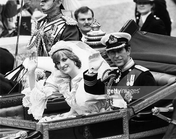 Princess Diana and Prince Charles of Wales wave to the crowd from their carriage following their wedding ceremony London England