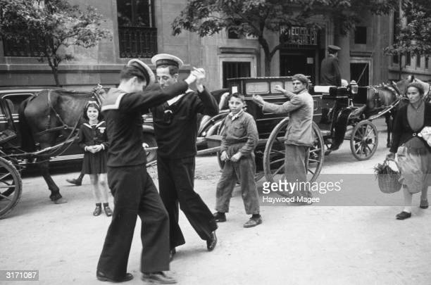 Two British sailors dance in a Spanish street to the music of a barrel organ Original Publication Picture Post 4101 Inside Spain pub 1946