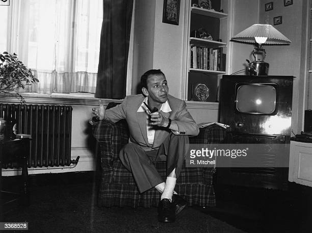 Popular American singer Frank Sinatra relaxing with a pipe at his flat in Mayfair, London, before his concert at the Palladium.