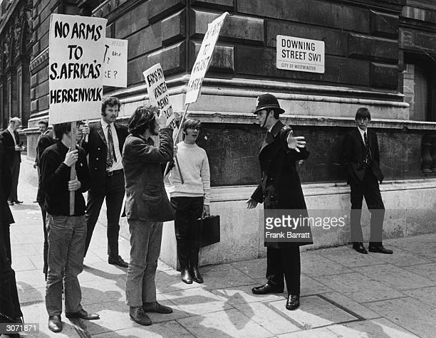 A policeman bars the way to Downing Street to a group of antiApartheid demonstrators protesting against the supply of arms to South Africa