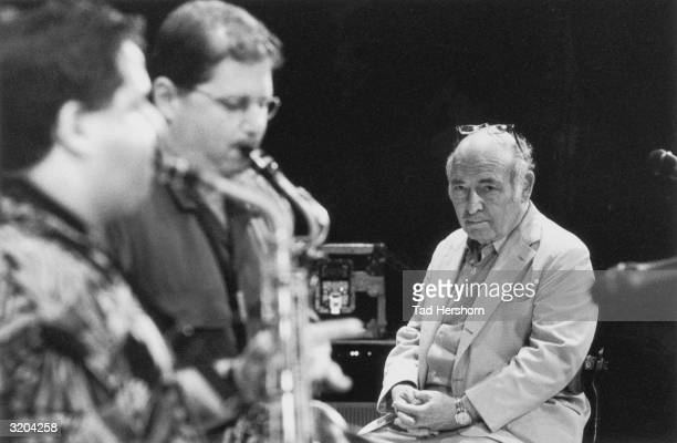 American jazz impresario and pianist George Wein watching two saxophone players on stage during the JVC Jazz Festival that he organized and founded...