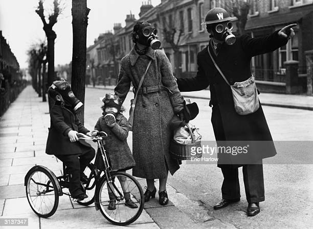A warden gives directions to a mother and her two children during a World War II gas drill in Southend