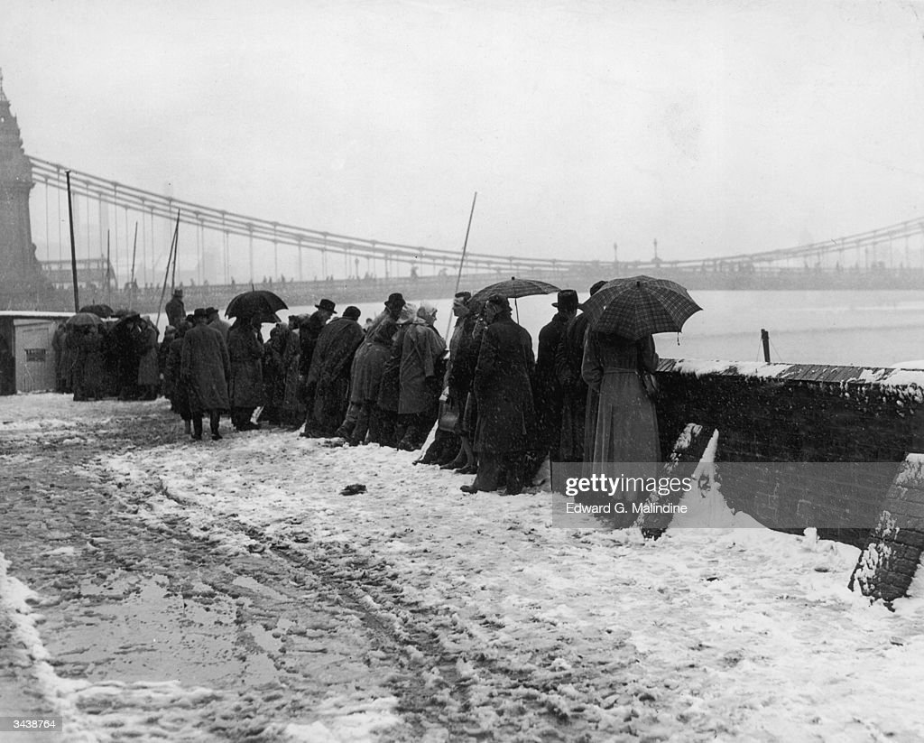 Spectators brave the cold on the towpath near Hammersmith Bridge, west London, to watch the Oxford and Cambridge University boat race.