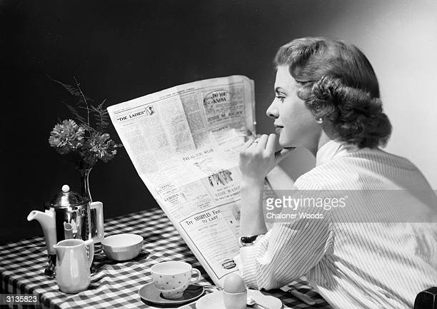 A woman wearing a striped shirt blouse reads a newspaper over the breakfast table before tackling her boiled egg and coffee