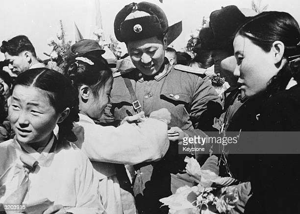 Korean girls present a member of the Chinese People's Volunteer Army with a bouquet of flowers prior to the mass withdrawal of Chinese troops from...