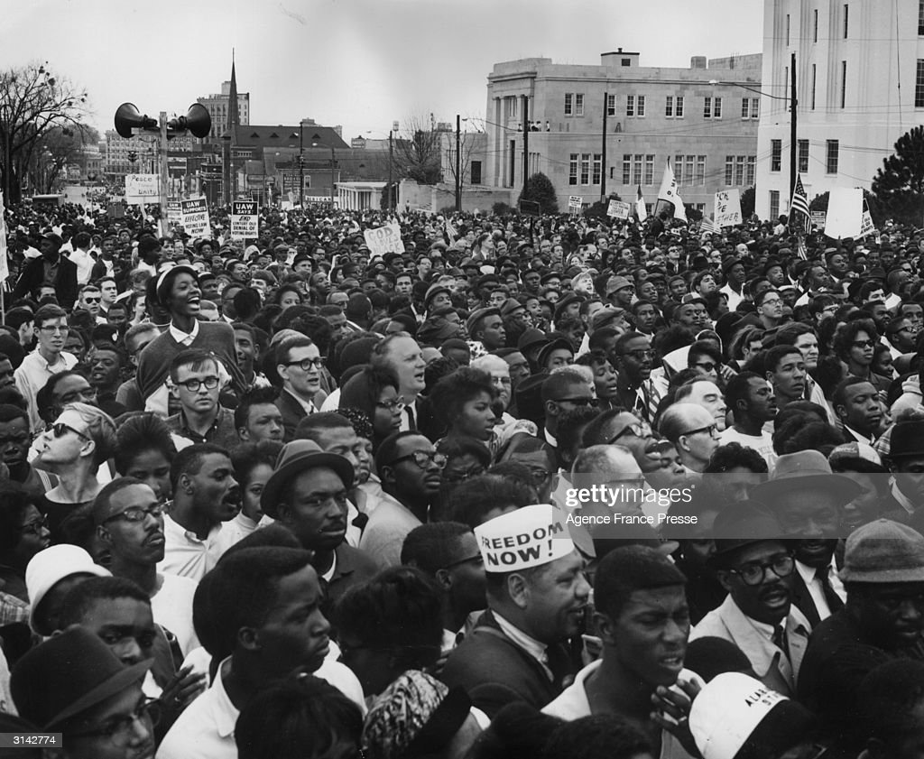 Civil rights protesters in Montgomery, Alabama after their march from Selma to protest against voter registration laws in the state. One marcher is wearing a hat with the slogan 'Freedom Now !' written on it.