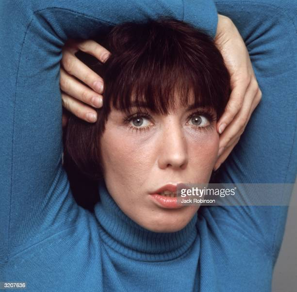 Studio headshot portrait of American comedian and actor Lily Tomlin with her arms wrapped around her head She wears a turquoise blue turtleneck...