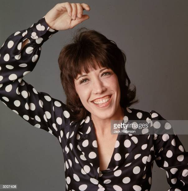 Studio portrait of American comedian and actor Lily Tomlin smiling while holding one hand over her head. She wears a black blouse with large white...
