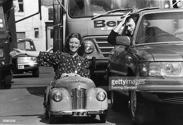 Blue Peter presenter Lesley Judd driving a toy car an AJ40 in a busy London street The car is worth about £200