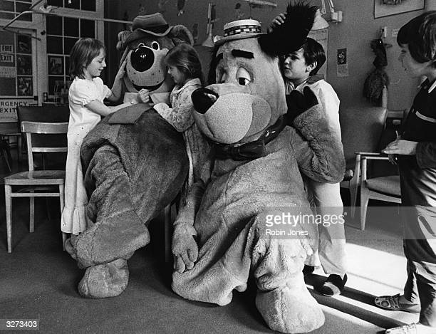 Children playing with people dressed as 'Huckleberry Hound' and 'Yogi Bear' during their visit to the Royal National Nose Throat And Ear Hospital