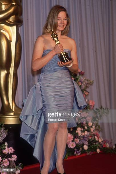 American actor Jodie Foster smiles and holds her Best Actress Oscar in front of a blue curtain at the Academy Awards, Los Angeles, California. She...