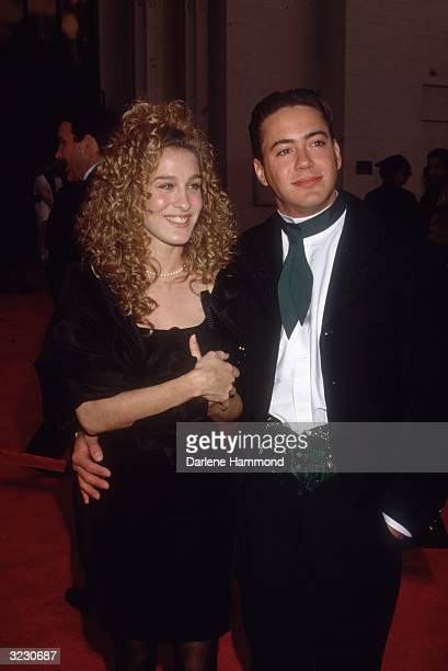 American actor Sarah Jessica Parker smiles, holding hands with her boyfriend, American actor Robert Downey, Jr., as they arrive at the Academy...