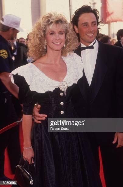 British-born Australian pop singer Olivia Newton-John and her husband, actor Matt Lattanzi, smile as they arrive at the Academy Awards, Shrine...