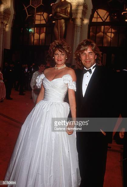 Married American actors Don Johnson and Melanie Griffith pose together as they arrive at the Academy Awards, Shrine Auditorium, Los Angeles,...