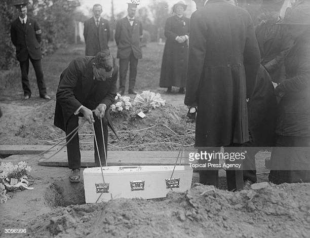 Mrs and Miss Dickin watch as a child's coffin is lowered into a grave at the funeral of Folkestone airraid victims