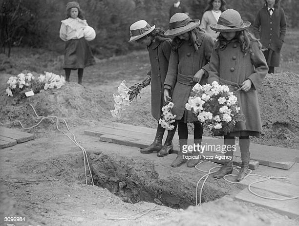 Schoolgirls holding flowers look down into a freshly dug grave at the funeral of Folkestone airraid victims