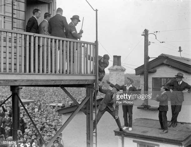 Enthusiastic supporters climbing onto a shed roof to as Captain Charles Lindbergh climbs down from the control tower at Croydon Airport, England. He...