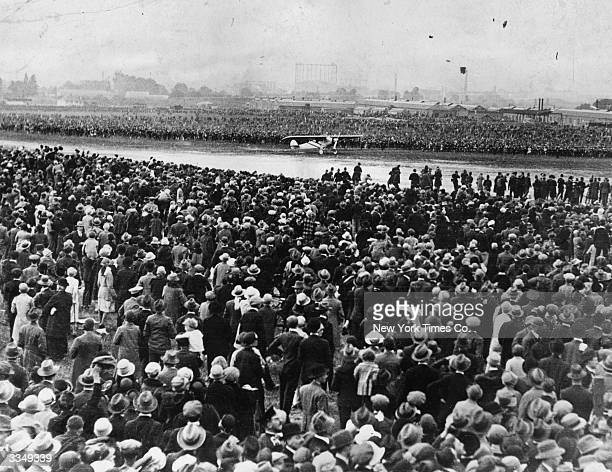 Thousands of spectators watch Charles Lindbergh arriving at Croydon London in his Ryan 'Spirit Of St Louis' soon after completing the first direct...
