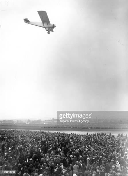 US aviator Charles Lindbergh's aeroplane flying above welcoming crowds at Croydon aerodrome following his recordsetting nonstop solo transatlantic...