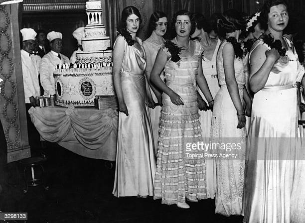 Debutantes in their finery bring in the giant birthday cake at the Queen Charlotte's Birthday Ball at the Dorchester, London.
