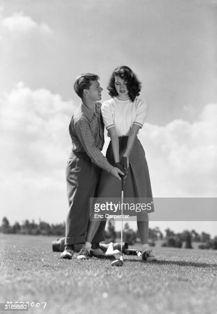 Actress Ava Gardner takes a golfing tip from her husband former child actor Mickey Rooney