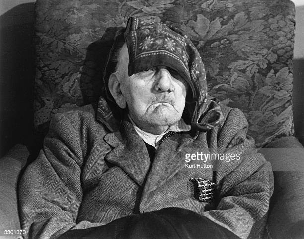 An elderly resident of the Bishopswood Home in Highgate north London having a rest in an armchair with his handkerchief shielding his face Original...