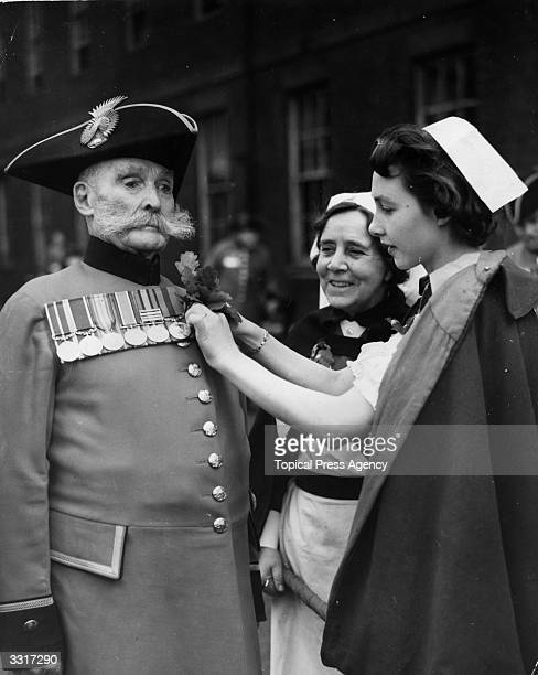 Former Irish Guard having oak leaves pinned on to his uniform by a nurse of the Royal Hospital, before a visit by Field Marshal Sir William Slim to...