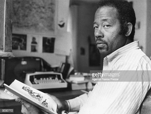 American author and former Black Panthers head Eldridge Cleaver holds a book Paris