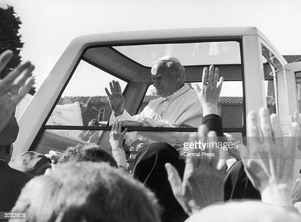 Pope John Paul II waves from the window of his 'Popemobile' during a visit to Digby Stuart Catholic College in Roehampton London