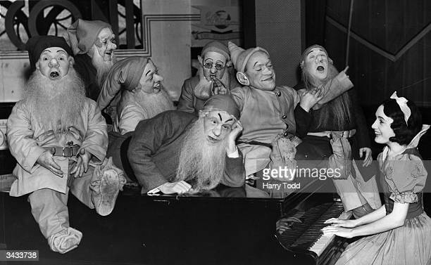 A group of actors dressed as Snow White and the Seven Dwarves entertain the Christmas shoppers at a store in London's Clapham Junction