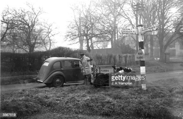 An AA patrolman advises on an alternative route avoiding the flooded roads around Laddington in Kent