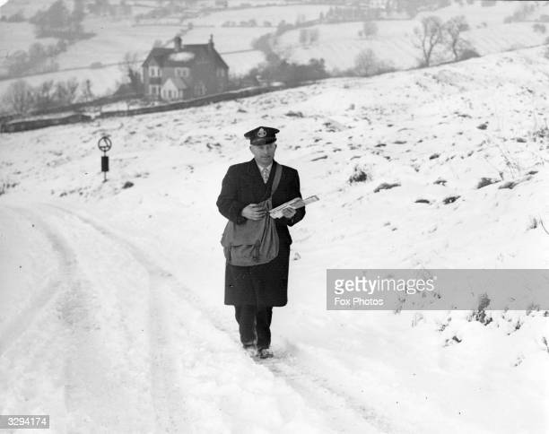 Notwithstanding the inclement weather 'Postman Paddy' continues to deliver the Queen's mail near Woodmanscote in Gloucestershire
