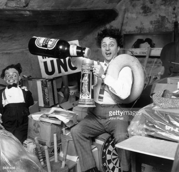 Liverpudlian comedian Ken Dodd sorts through a heap of junk including a ventriloquist's dummy an old tankard and a giant beer bottle in the attic of...