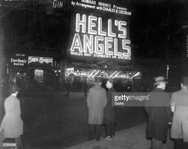 An exterior view of a West End cinema and its neon sign showing the Howard Hughes production 'Hell's Angels'