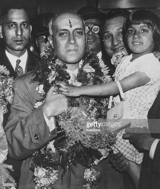 A garlanded Jawaharlal Nehru on parole from political imprisonment arrives at Victoria station London to a hero's welcome