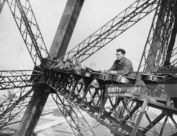 Electrical workers balance high up on the Eiffel tower in paris to change the lights that illuminate the tower at night