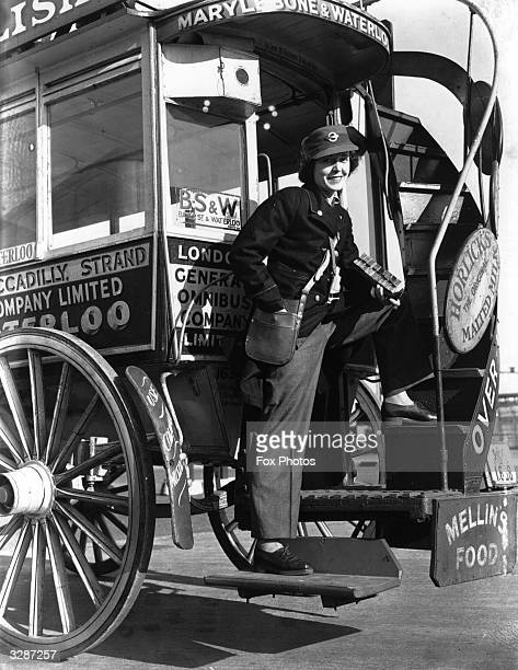 One of the first London women bus conductors issued with new winter uniform of slacks and three quarter length coats operating on an old horse pulled...