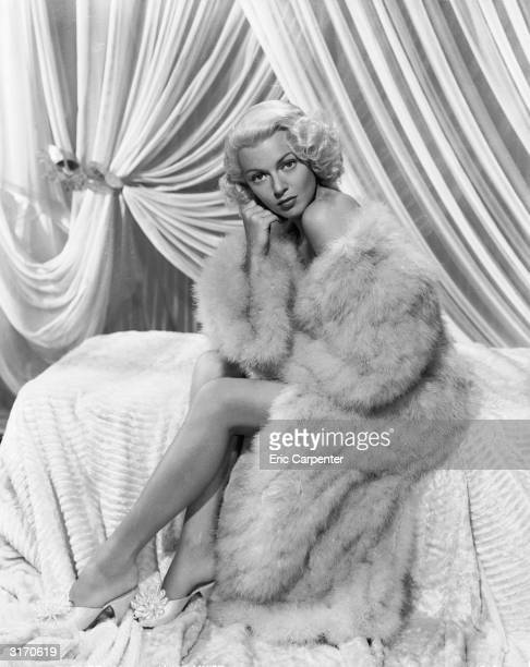 Hollywood actress Lana Turner wrapped in a sensuous fur coat