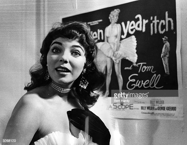 Joan Collins the British leading lady, who went on to become an international star, posing in front of a poster for the 'Seven Year Itch'. Original...