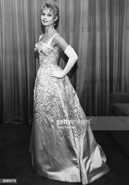 French actress Brigitte Bardot wearing a classical white satin dress embroidered with sequins and pearls at a Royal Film Performance at the Empire in...
